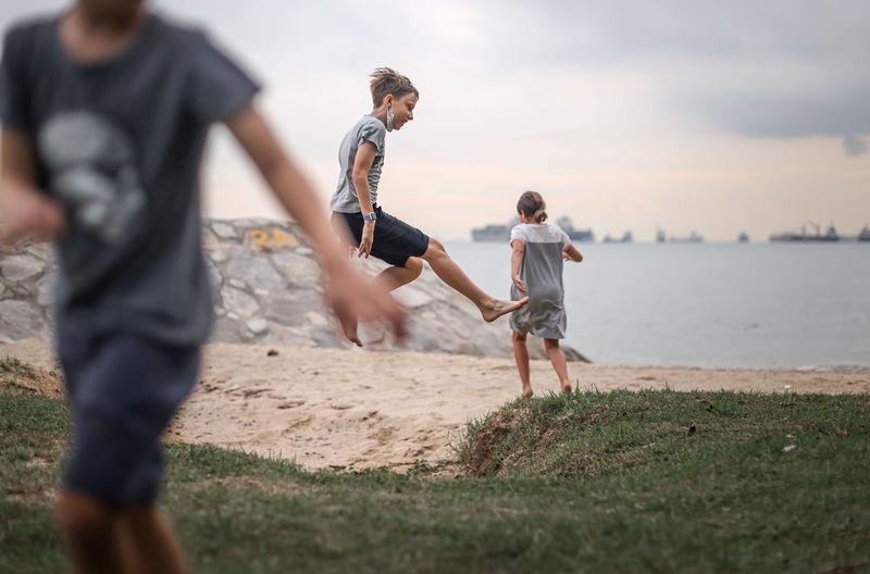 Rear view of men running on beach