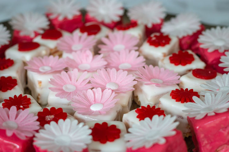 Colorful petit fours with flower decoration Flower Freshness Close-up Red Fragility Petal No People Vulnerability  Beauty In Nature Large Group Of Objects Selective Focus White Color Indoors  Pink Color High Angle View Inflorescence Abundance Flower Head Temptation Decoration Petit Fours Petit Four Sweet Food