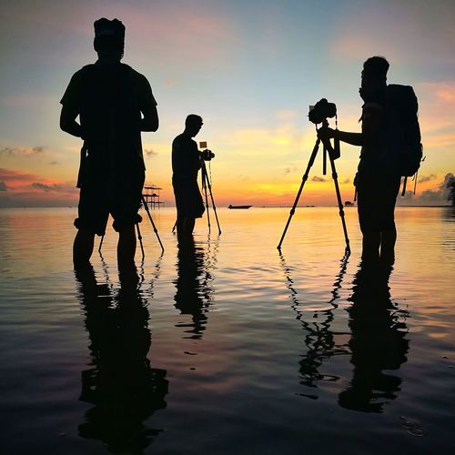 Silhouette People Photographing While Standing In Sea Against Sky During Sunset