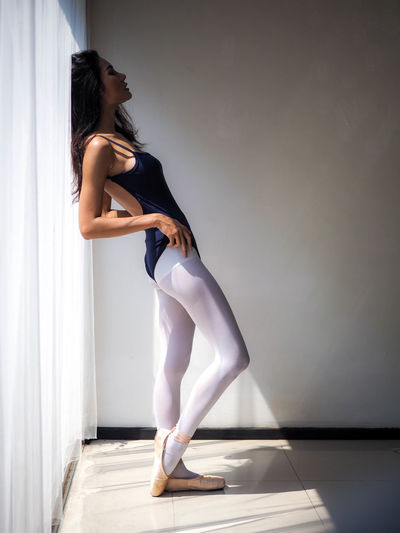 Full length of ballet dancer standing against curtain at home