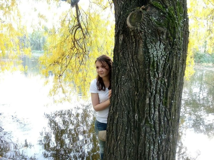 Thoughtful Woman Hiding Behind Tree By Calm Lake