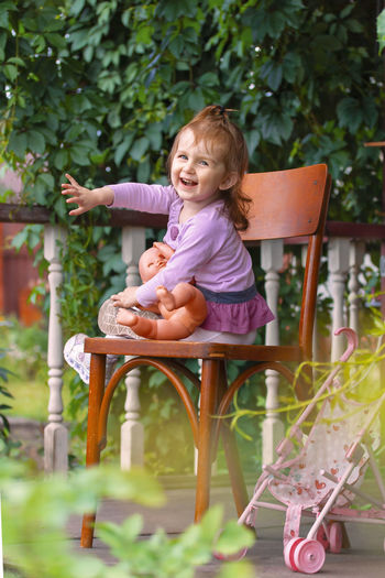 Girl sitting on chair against plants