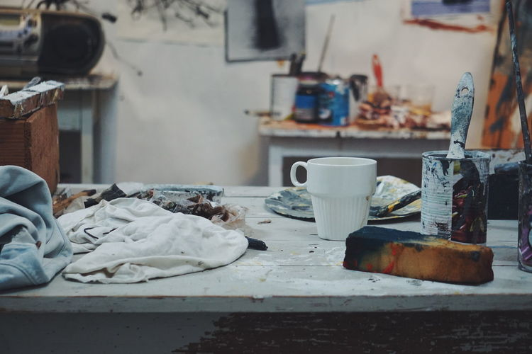 Messy painting equipment on table at workshop