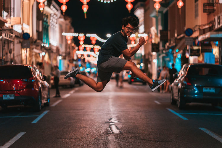 Man jumping on street at night