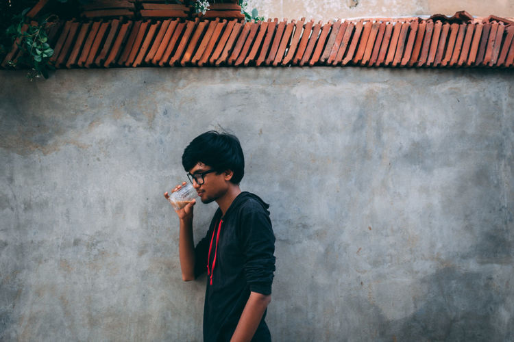 Side View Of Young Man Drinking Coffee While Standing Against Wall