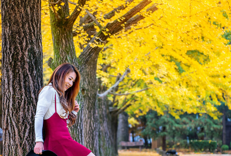 Woman standing by tree during autumn