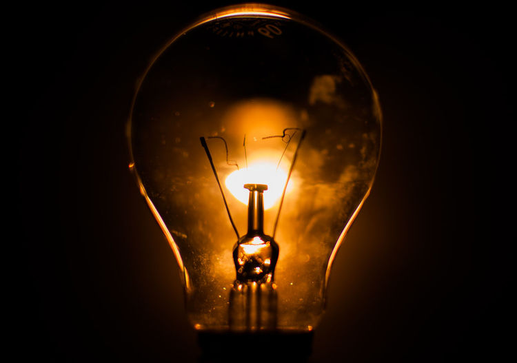 Close-Up Of Illuminated Light Seen Through Bulb Against Black Background