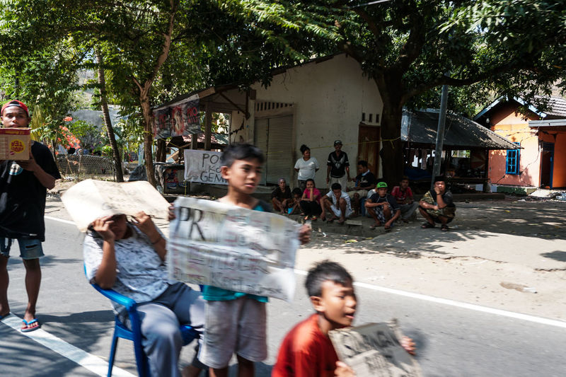 Indonesia, Lombok Island West Nusa Tenggara (NTB), on Sunday (5/8/2018) at around 6:46 p.m., the earthquake with a strength reached 7.0 on the Richter Scale (SR). The photo was taken 3 days after the earthquake along the road to North Lombok which suffered the worst damage. residents make emergency tents along the main road and wait for government assistance and donations from volunteers. the situation in Lombok is still severe, making traffic jams everywhere, scrambling for help to survive. Group Of People Street Building Exterior Architecture Tree City Women Plant Real People Men People Day Built Structure Nature Adult Incidental People Leisure Activity Walking Outdoors Landscape Lombok Lombok-Indonesia Lombok Island Earthquake Earthquake Area