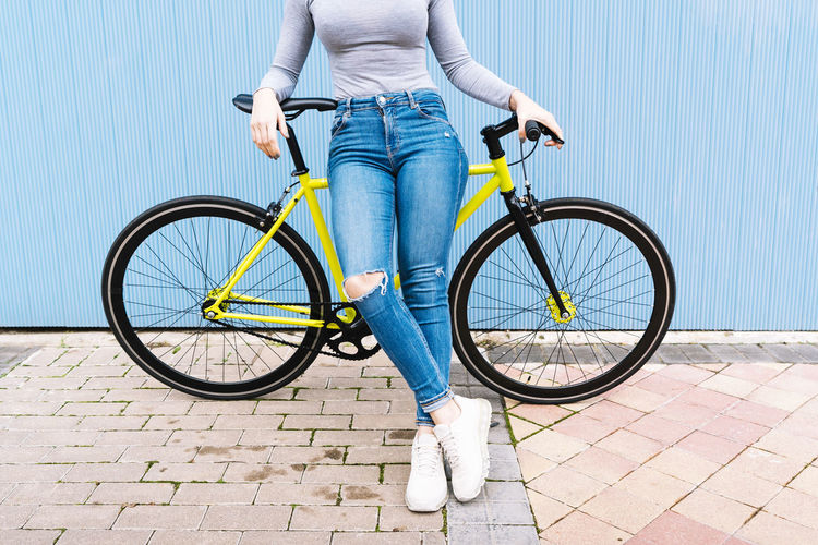 Low section of woman riding bicycle