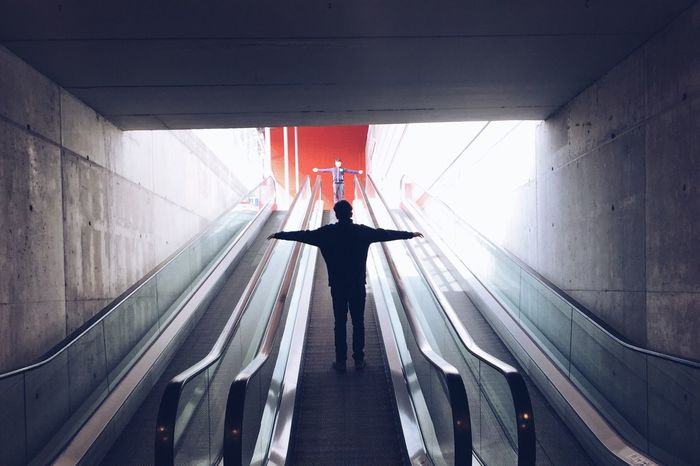 People with arms outstretched while standing on escalator
