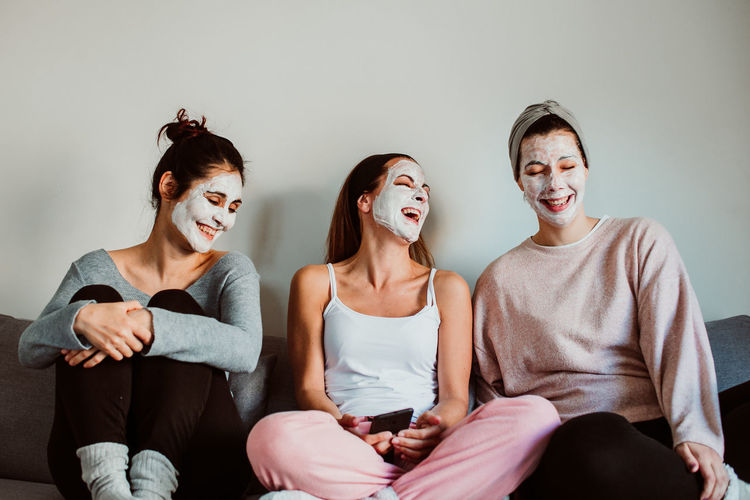 Cheerful female friends with facial masks sitting against wall at home