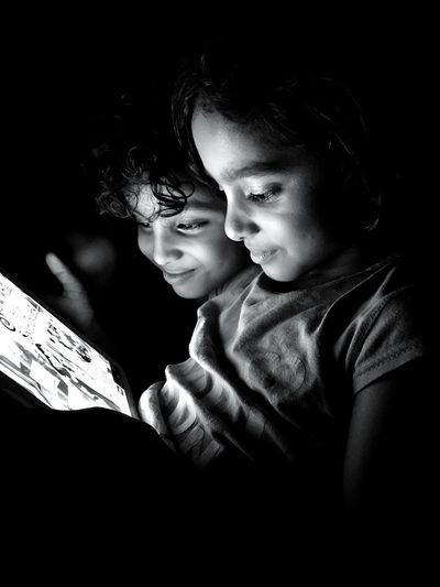 Smiling Cute Siblings Playing On Digital Tablet In Darkroom