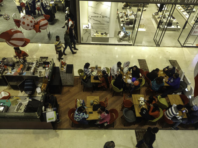This is in the ground level of the DLF Mall of India in Noida, North India. There are these drinks and short eats counters spread at different locations, for people to sit down and have something to eat and drink, while resting as well, or taking a break from shopping. This is an overhead view, with the glass doors of shops visible, along with some Christmas decorations. Eating Eating Indoors India Mall Of India Refreshments Cafe Cafe Time Coffee Break Consumerism Indoors  Indoors Restaurant Large Group Of People Men Noida People Real People Restaurant Retail  Store Women