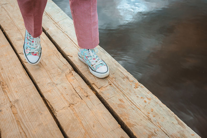 Low section of person standing on pier over lake