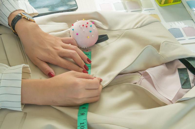 Midsection of fashion designer stitching jacket at workshop