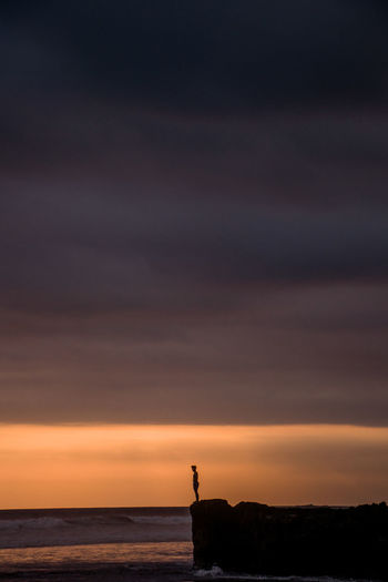 Silhouette person standing on cliff against sea during sunset