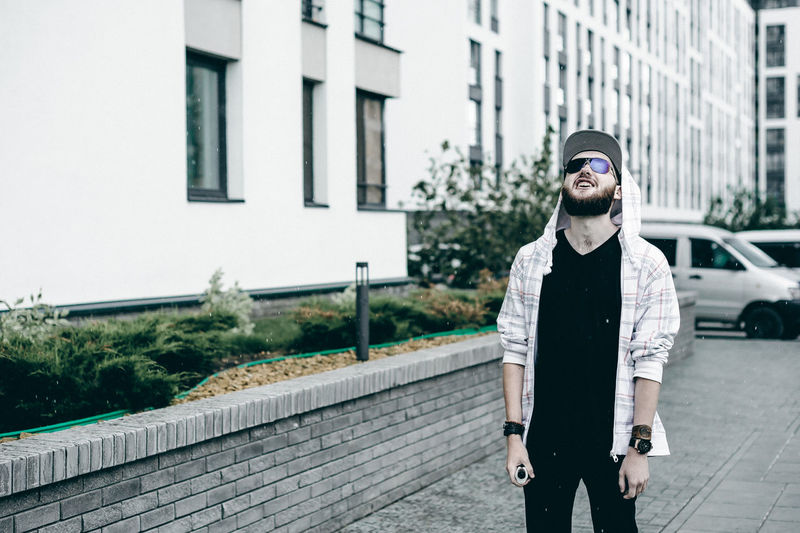 Vaping Adult Architecture Beard Building Exterior Built Structure Casual Clothing City Day Front View Hands In Pockets Happiness Human Hand Leisure Activity Lifestyles Looking At Camera Men One Person Outdoors People Portrait Real People Smiling Young Adult Young Men