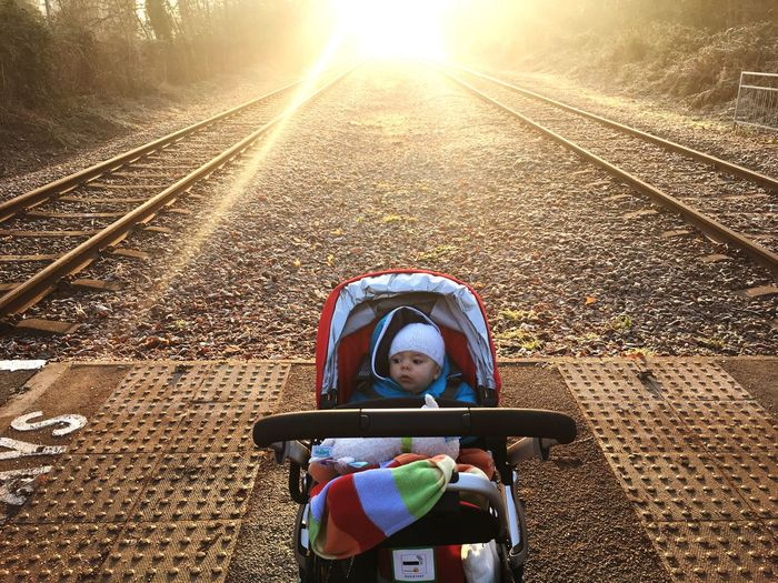 Baby In Stroller Waiting For The Tram During A Winters Morning Sunrise. Mitcham, England. Crossing Distance Perspective Kid Stroller Pram Dusk Future Vision Future Landscape Sunset Sunrise London Mitcham Phipps Bridge Tram Travel Railway Rail Train Tram Toddler  Baby Child Male Boy Railroad Track Transportation Sunlight Childhood Outdoors Mobility In Mega Cities
