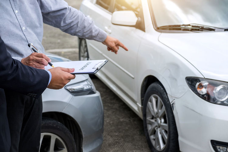 Midsection of man signing on car insurance paper