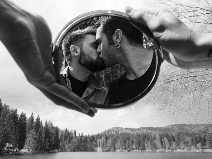 Men Kissing On Mouth Reflecting In Mirror Held By Hands
