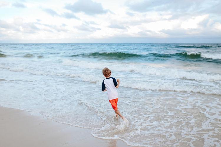 Full length of boy running on beach against sky