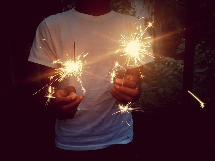 Midsection Of Man Holding Sparklers While Standing In Yard