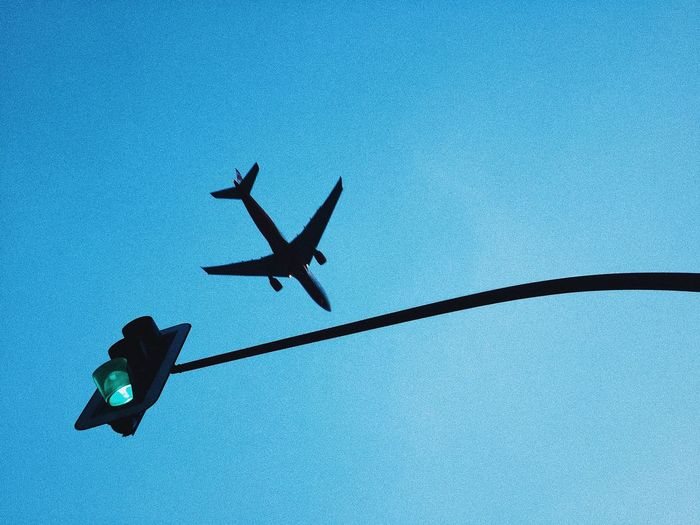 Low Angle View Of Silhouette Airplane Flying Against Clear Blue Sky