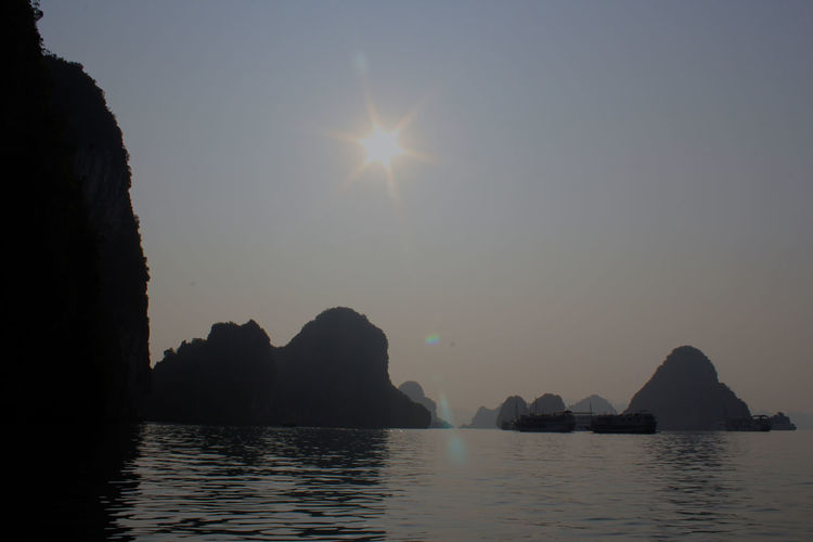 Silhouette Boats On Halong Bay By Rock Formations Against Clear Sky