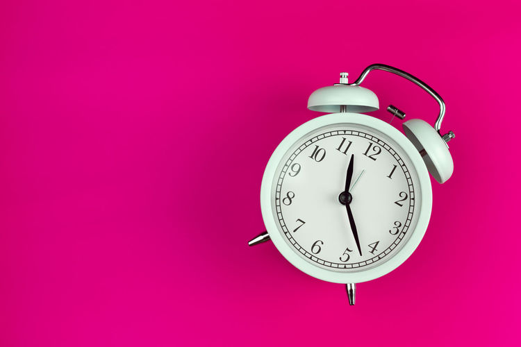 Close-up of clock over pink background