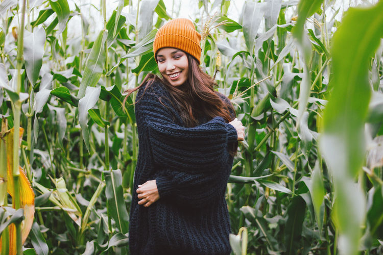 Smiling young woman amidst plants