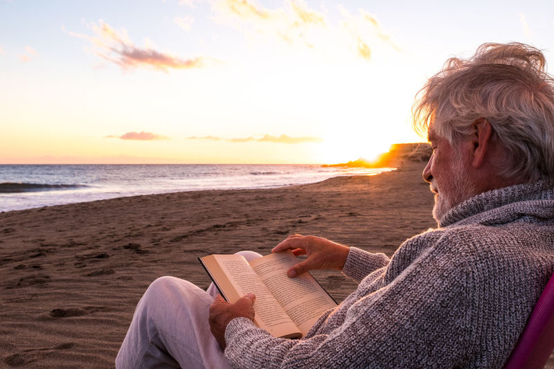 Man sitting on book at beach against sky during sunset