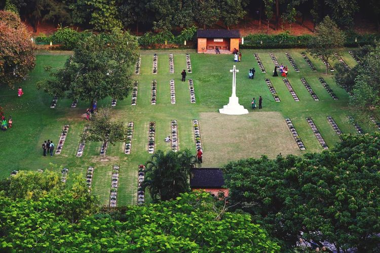 High Angle View Of People And White Cross On Field In Cemetery