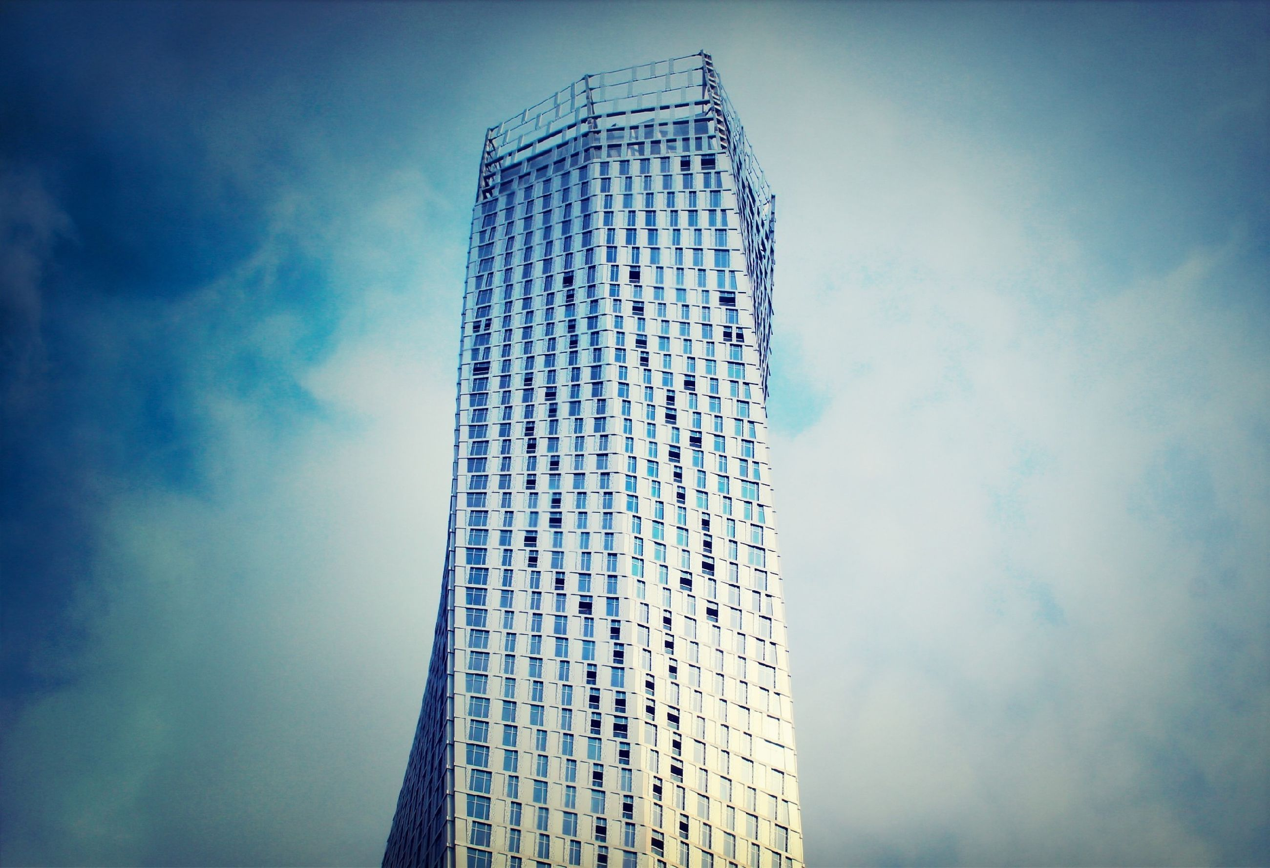 low angle view, sky, building exterior, architecture, built structure, modern, tall - high, cloud - sky, skyscraper, blue, office building, tower, city, cloud, building, tall, day, outdoors, cloudy, no people