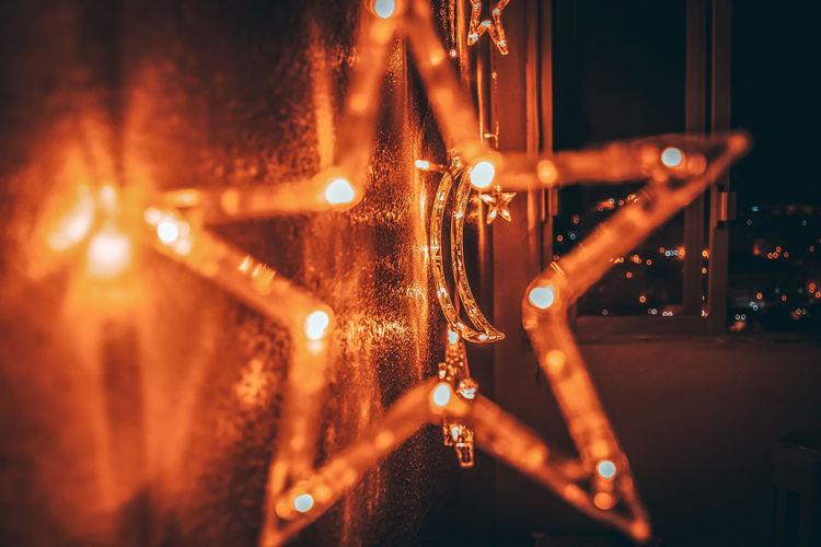 Close-up of illuminated star shape by wall