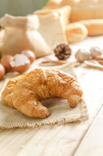 Close-up of croissant and ingredients on table