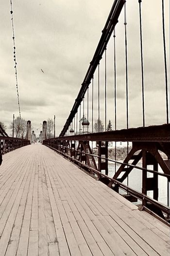View of suspension bridge against cloudy sky