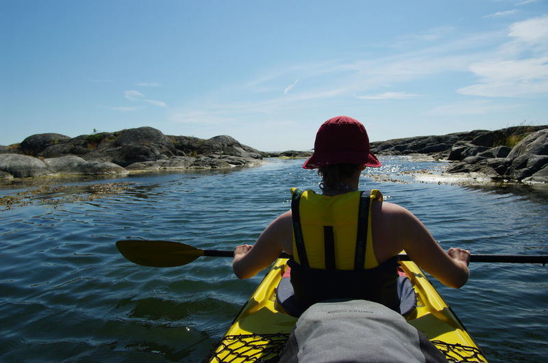 Rear view of man sitting in kayak