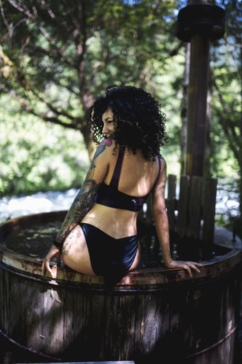 Rear view of woman sitting in wooden hot tub