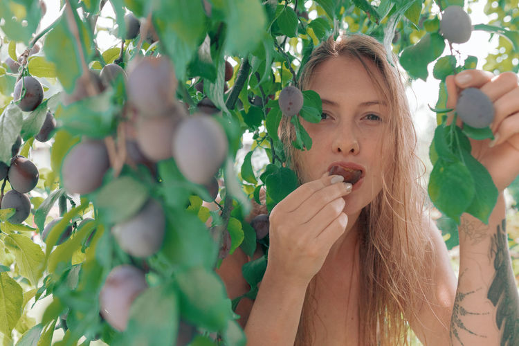 Portrait of young woman eating berries while standing by tree