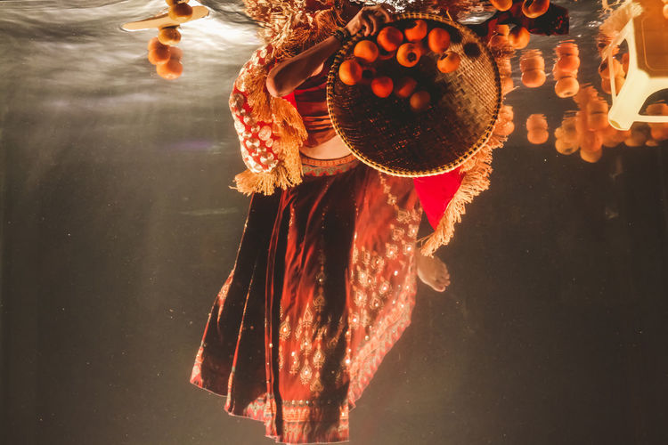 Low section of woman wearing traditional clothing underwater