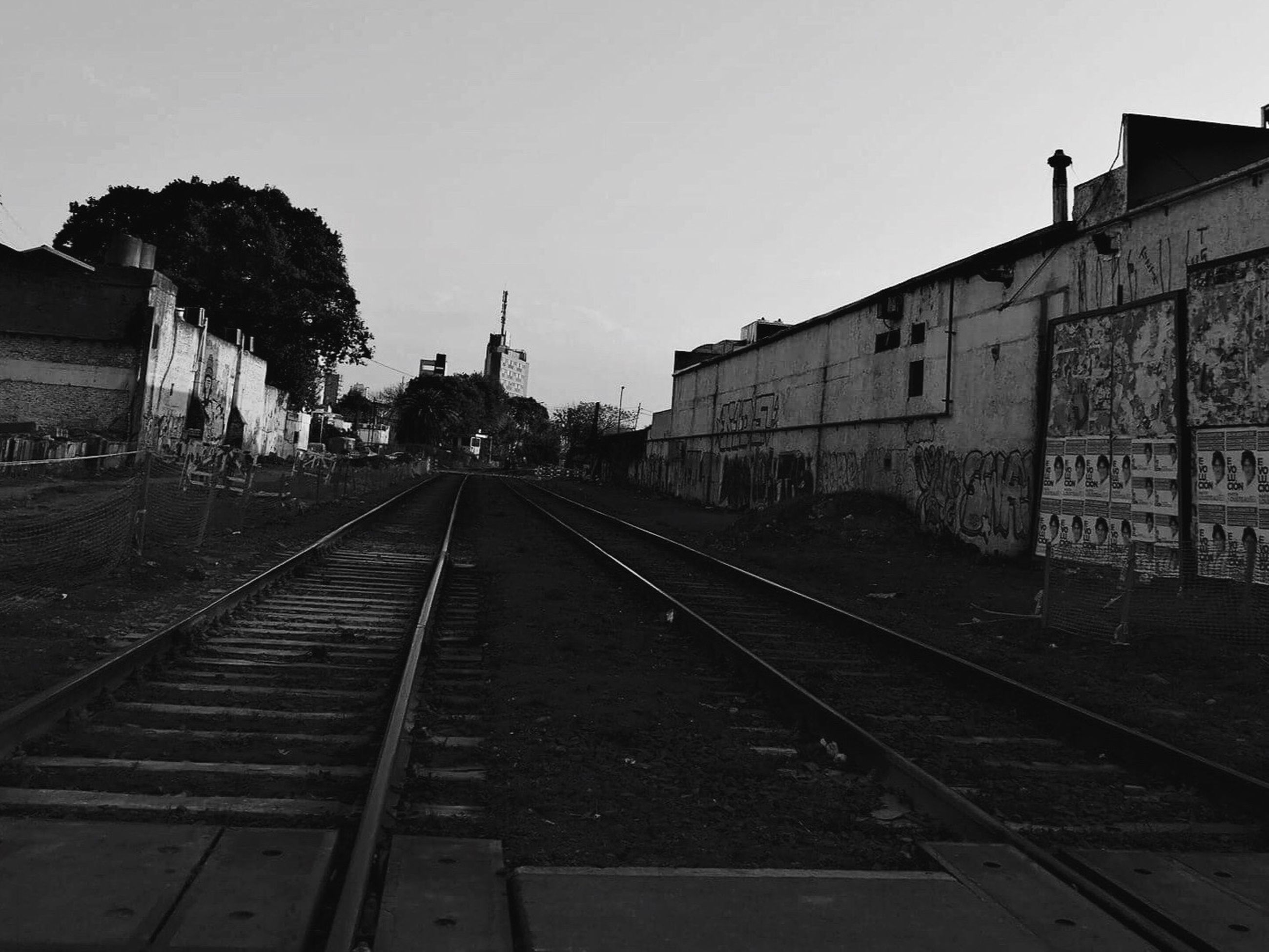 railroad track, transportation, rail transportation, built structure, architecture, clear sky, building exterior, sky, outdoors, day, public transportation, no people