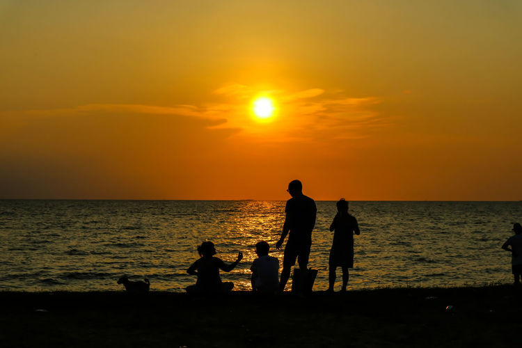 silhouette people family and pet meeting at beach and sea sand sunset background Family Family Party Holiday Relaxing Sunlight Sunset Silhouettes Sunset_collection Beach Beachphotography Beauty In Nature Family Pet Family Portrait Family Time Horizon Horizon Over Water Leisure Activity Outdoors Real People Scenics - Nature Sea Sea And Sky Sky Sunset This Is Family Water