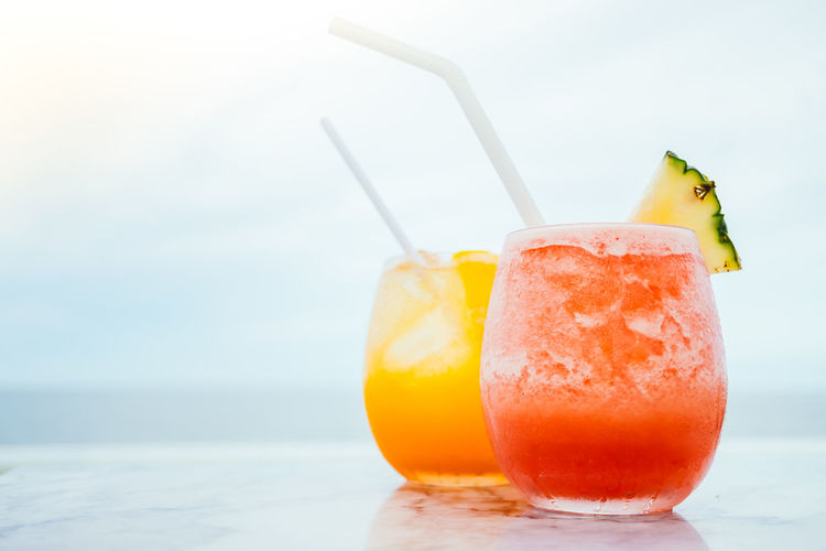 Close-up of drinks on table against sea