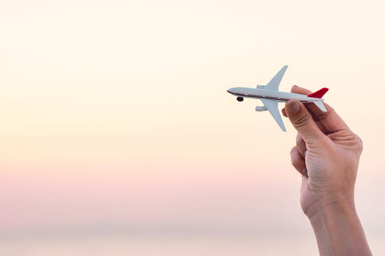 Woman hand holding airplane model in sunset sky and summer sea background dreams of journey in vacation. Travel and air transportation concept. Taking flight and takeoff, Hand with small toy plane. Take Off Vacations Air Vehicle Airplane Clear Sky Copy Space Finger Flight Flying Hand Holding Human Body Part Human Hand Journey Lifestyles Men Nature One Person Personal Perspective Real People Sky Summer Sunset Transportation Travel