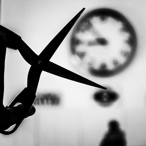Close-up of silhouette hand holding clock