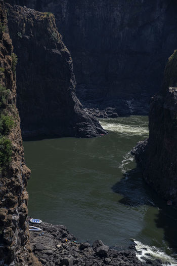 Scenic view of cliff and water in river