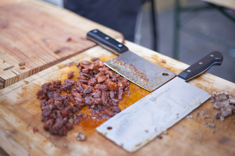 High angle view of chopped beef with knives on cutting board