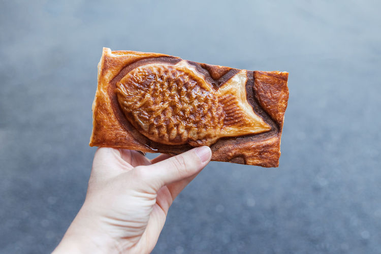 Close-up of hand holding taiyaki japanese dessert