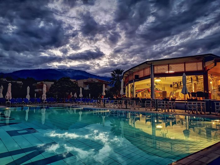 Water Swimming Pool Reflection Sky Architecture Building Exterior Built Structure Water Slide Water Park Dramatic Sky Swimming Lane Marker Moody Sky Thunderstorm Atmospheric Mood