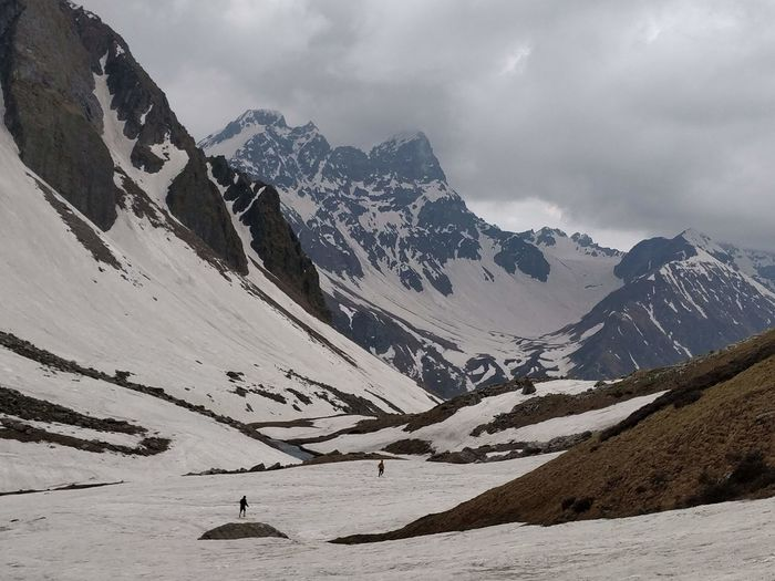 People walking on snow covered land against mountain range